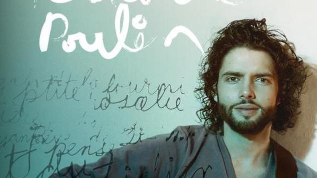 Alexandre Poulin regarde la caméra en face, une guitare à la main.