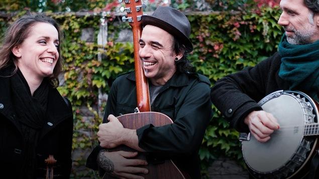 Les trois membres de la formation Bon Débarras (Marie-Pierre Lecault, Dominic Desrochers et Jean-François Dumas), à l'extérieur, tout sourire. Dominic, au centre, enlace sa guitare, alors que Jean-François, à droite, joue du banjo.