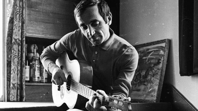 Charles Aznavour joue de la guitare, assis sur des marches, dans une maison.