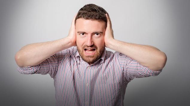 Une homme se bouche les oreilles
