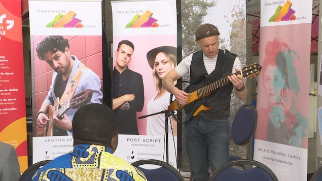 Un musicien joue de la guitare devant des affiches de l'organisme FrancoMusik.