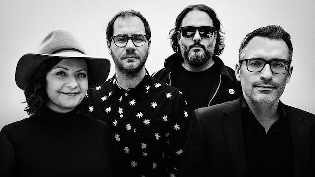 Une femme et trois hommes posent côte à côte sur une photo en noir et blanc.