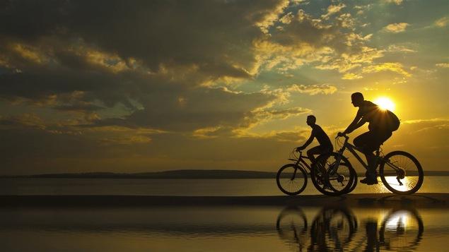 Un couple fait du vélo au couché du soleil près d'un lac.