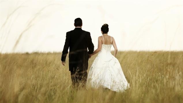 Un couple de jeunes mariés marche dans un champs.