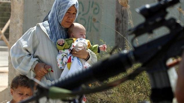 Une Palestinienne et ses enfants à un poste de contrôle de l'armée israélienne, en Cisjordanie