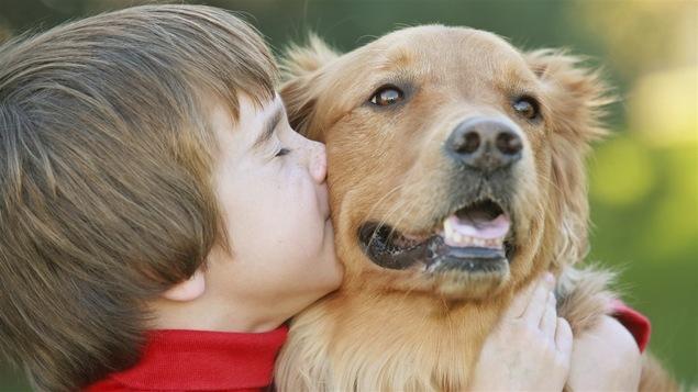 Un jeune garçon donne un câlin à son chien.