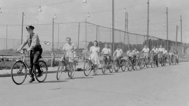 Des jeunes de Verdun roulent à la file indienne derrière un policier en 1941.
