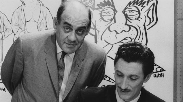 L'animateur Miville Couture et le chanteur Yoland Guérard posent devant des caricatures en 1959.