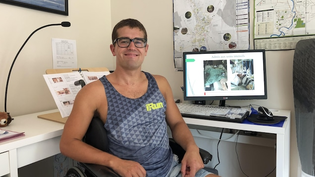Un jeune homme souriant assis dans un fauteuil roulant.