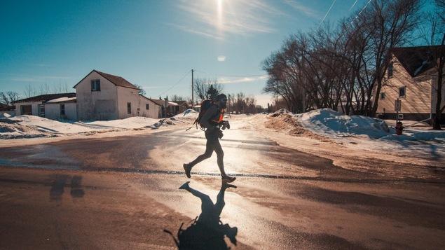 Un athlète barbu porte un sac à dos en courant dans la rue en plein hiver.