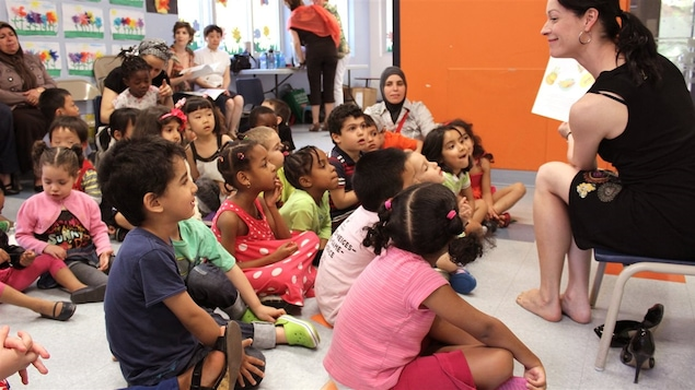 Des enfants assis par terre écoutent une histoire lue par une femme assise sur une chaise à l'avant