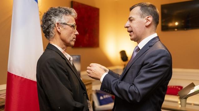 Une homme recoit une medaille d'un autre homme dans un bureau avec un drapeau de la France.