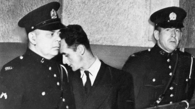 Albert Guay, à la cour entre deux policiers en 1949, pour l'affaire de l'explosion d'un avion au-dessus de Charlevoix, tuant 23 personnes.