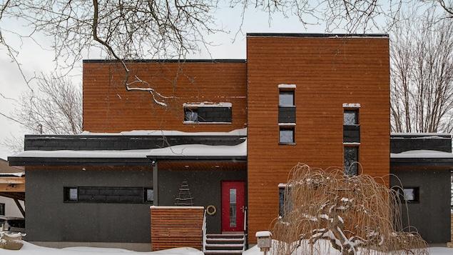 Une maison de briques rouges et noires sur deux étages avec plusieurs fenêtres.