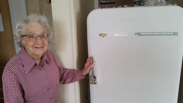 Alice Dupuis devant son réfrigérateur, le même depuis 1953