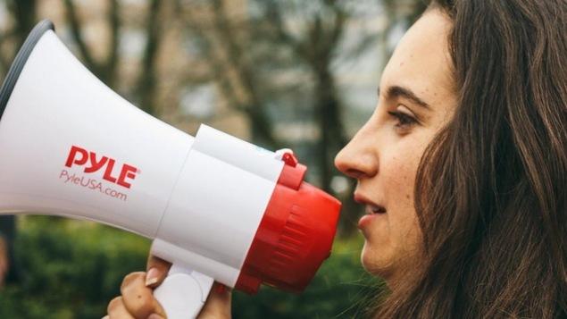 Une jeune fille parle dans un porte-voix.