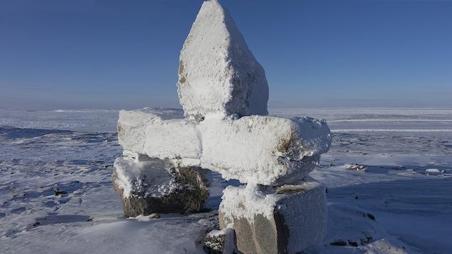 Un inukshuk recouvert de neige.