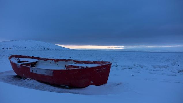 La coque d'un petit bateau pris dans la glace.