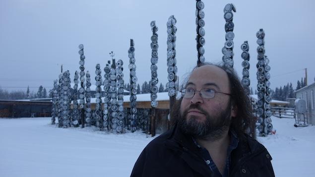 Un homme, le regard vers la gauche, pose devant des sculptures faites avec des jantes de voiture, dehors dans la neige.