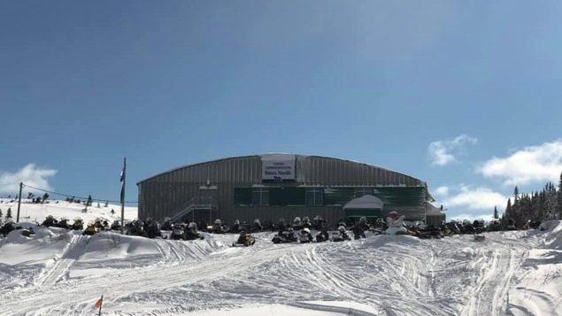 Centre communautaire Relais Nordik (aréna) à La Tabatière, sur la Basse-Côte-Nord, en hiver, avec de nombreuses motoneiges stationnées devant