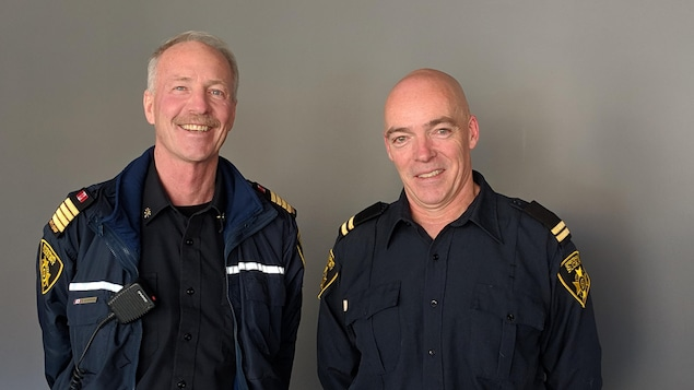 Deux pompiers, en uniforme dans le studio de Radio-Canada Sudbury.