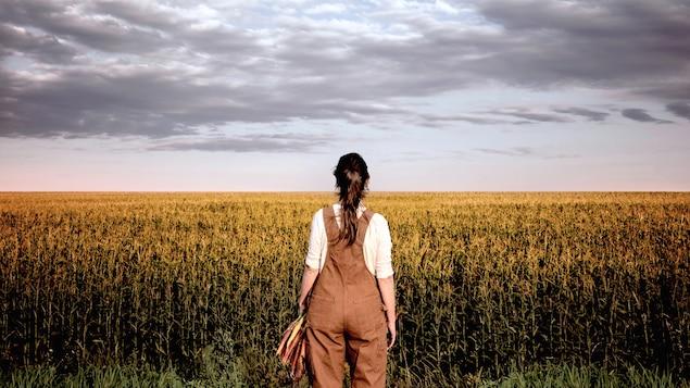 Une femme est posée de dos, face à un champ de maïs.