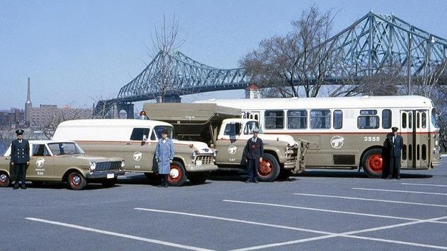 Photo d'époque de quatre véhicules bruns de la Société de transport de Montréal avec un homme debout devant chaque véhicule.
