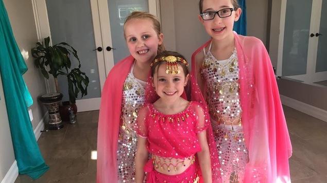 Trois jeunes filles de 6 à 9 ans portent des vêtements roses et blancs à paillettes pour danser le baladi.