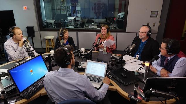 Six journalistes dans un studio de radio assis devant des micros autour d'une table.