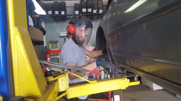 Un homme portant une visière en train de travailler sur la roue d'une voiture.