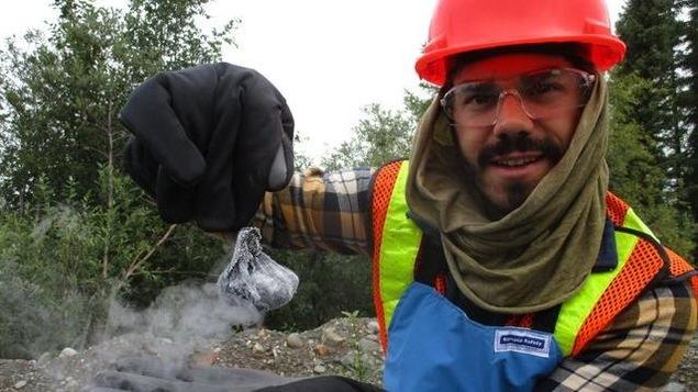 Un chercheur est dans la foret avec un casque route et tient avec des gros gants un objet qui fume.