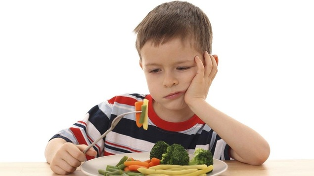 Enfant devant une assiette de légumes