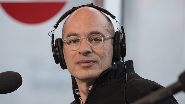 Bernard Werber, avec des écouteurs sur la tête, assis derrière un micro.