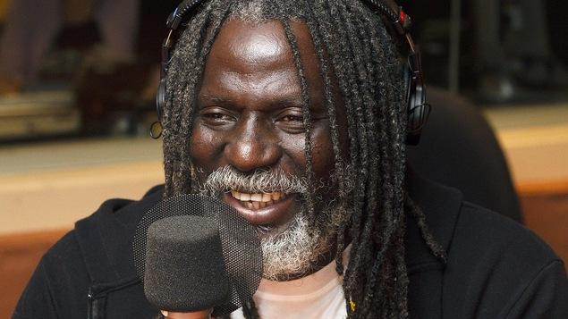 Un homme sourit devant  un micro.