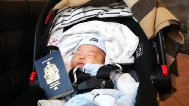 Un bébé dors dans un banc d'auto avec un passeport canadien.
