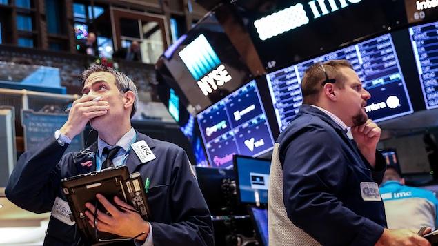 Des employés de la Bourse de New York observent leurs écrans avec inquiétude.