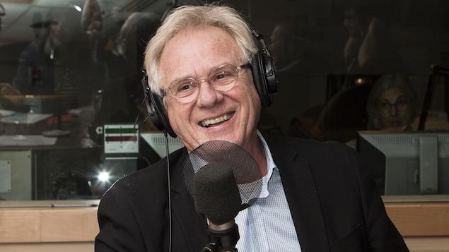 L'animateur Claude Saucier sourit au micro d'ICI Première.