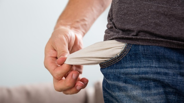 Un homme sort la doublure de sa poche vide.