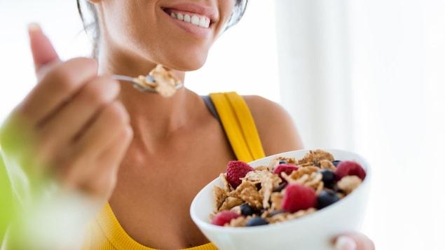 Une femme à l'apparence saine déguste un bol de céréales en souriant.