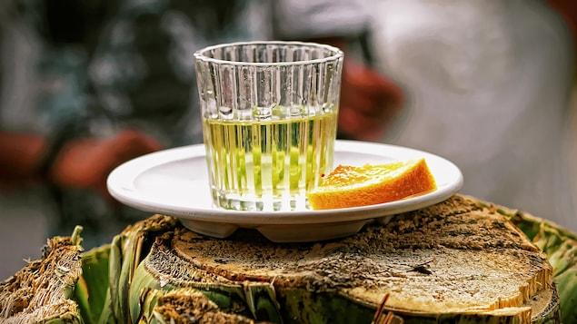 Un verre de mezcal est accompagné d'un quartier d'orange.