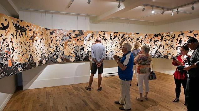 Six personnes sont devant une toile artistique dans un musée.