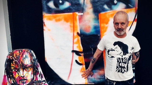 L'artiste Zïlon pose à côté de deux de ses œuvres.