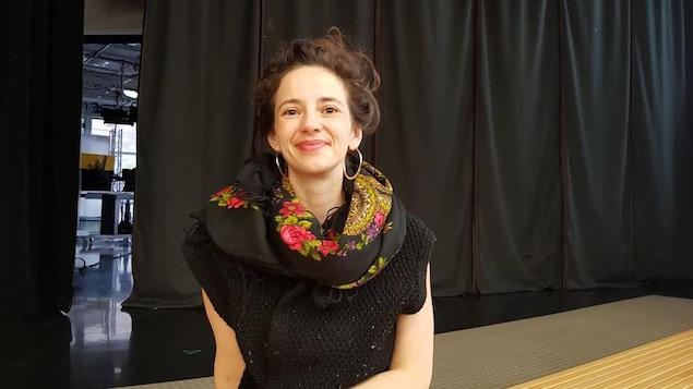 Une femme est photographiée devant un rideau noir.