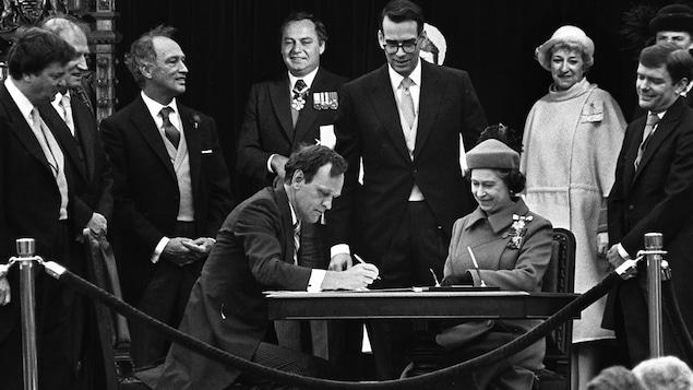 Jean Chrétien signe le rapatriement de la Constitution canadienne le 17 avril 1982, sous les yeux de la reine Elizabeth II.