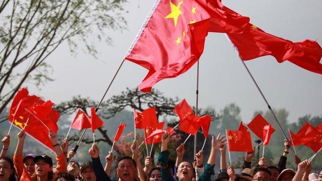 Photo d'une foule agitant des drapeaux chinois.