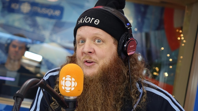 Un homme à la barbe rousse parle devant un micro orange.