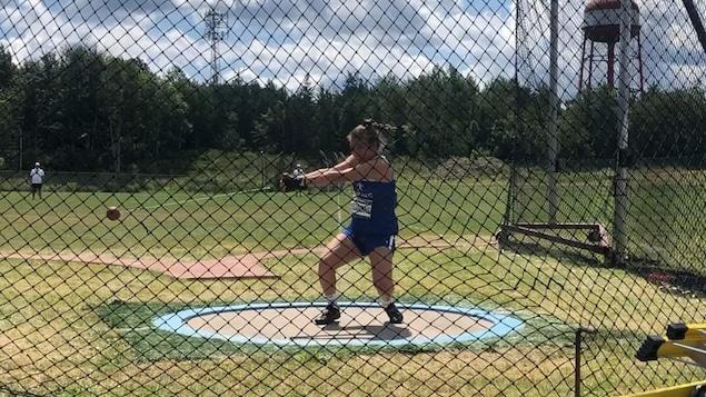 La jeune athlète Camille Desjardins en train de faire un lancer du marteau, sur un terrain dehors.
