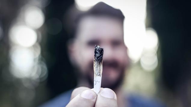 Un homme tient un joint de cannabis entre ses doigts et il le montre en avant de lui.