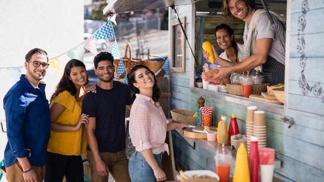 Des gens sourients pendant qu'ils se font servir dans un casse-croute