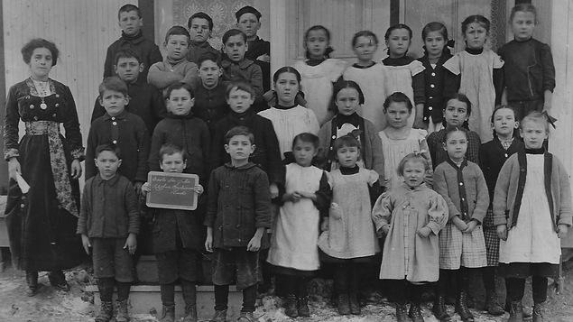 Une maîtresse d'école se tient debout à côté de ses élèves.